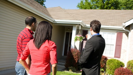 Couple talking to real estate agent about purchasing a property.